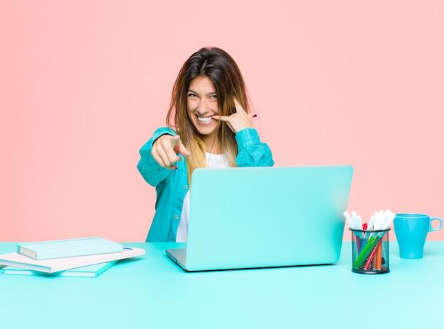 Die junge hübsche frau, die mit einem laptop freundlich lächelt und auf kamera beim tätigen eines anrufs sie zeigt, gestikulieren später und sprechen am telefon Premium Fotos