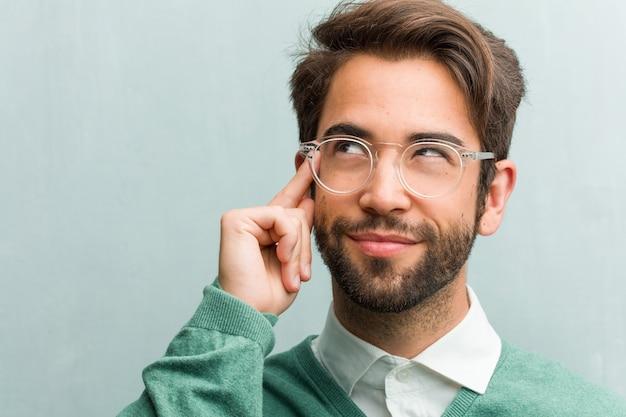 Die junge hübsche unternehmermann-gesichtsnahaufnahme, die oben verwirrt über eine idee denkt und schaut, würde versuchen, eine lösung zu finden Premium Fotos