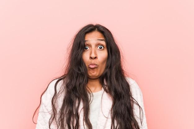 Die junge indische frau, die pyjama trägt, zuckt mit den schultern und die offenen augen, die verwirrt werden. Premium Fotos