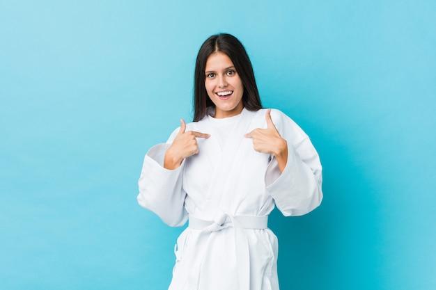 Die junge karatefrau zeigte überrascht auf sich selbst und lächelte breit. Premium Fotos