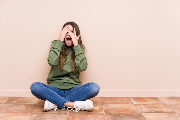 Die junge kaukasische frau, die auf dem fußboden sitzt, lokalisierte blinzeln durch die finger, die erschrocken und nervös sind. Premium Fotos