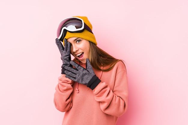 Die junge kaukasische frau, die einen ski trägt, kleidet lokalisiertes blinken durch die erschrockenen und nervösen finger. Premium Fotos