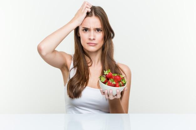 Die junge kaukasische frau, die erdbeerschüssel entsetzt hält, hat sie sich an wichtige sitzung erinnert. Premium Fotos