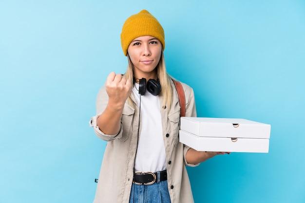 Die junge kaukasische frau, die pizzas hält, lokalisierte das zeigen der faust zur kamera, aggressiver gesichtsausdruck. Premium Fotos