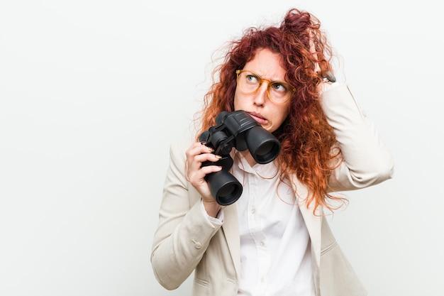 Die junge kaukasische geschäftsrothaarigefrau, die ein fernglas hält, das entsetzt ist, hat sich an wichtige sitzung erinnert. Premium Fotos
