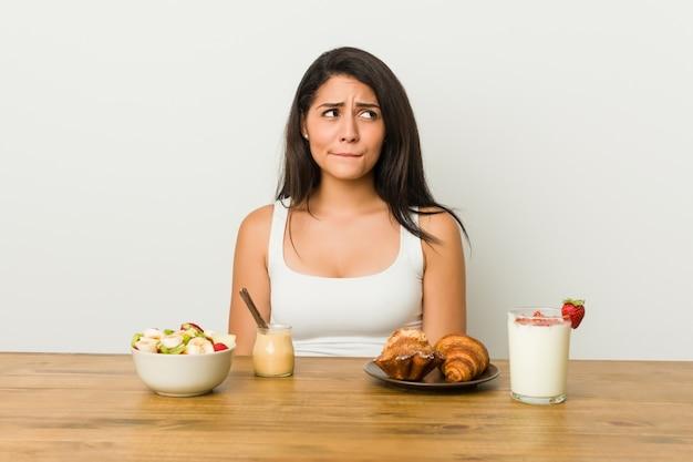 Die junge kurvige frau, die ein verwirrtes frühstück nimmt, fühlt sich zweifelhaft und unsicher. Premium Fotos