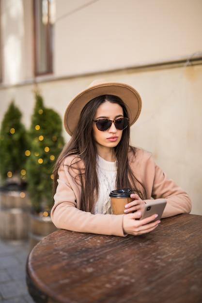 Die junge model-dame sitzt auf dem tisch in café-kleidern in dunkler sonnenbrille mit kaffeetasse und telefon Kostenlose Fotos
