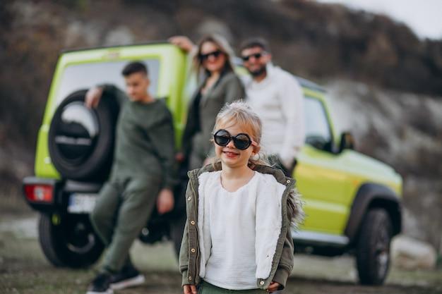 Die junge moderne familie, die mit dem auto reist und hielt für einen spaziergang im park an Kostenlose Fotos