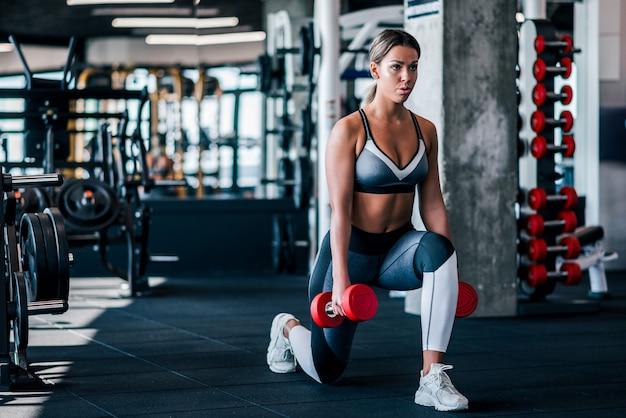 Die junge muskulöse frau, die ausfallschritte tut, trainieren mit dummköpfen in der turnhalle. Premium Fotos