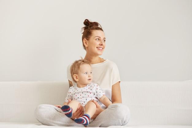 Die junge mutter mit ihrem einjährigen kleinen sohn im pyjama entspannt sich Kostenlose Fotos