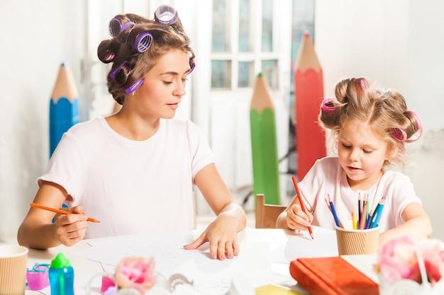 Die junge mutter und ihre kleine tochter zeichnen zu hause mit bleistiften Kostenlose Fotos