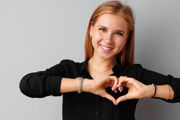 Die junge nette frau, die ihr herz mit ihren händen berührt, überreicht grauen hintergrund Premium Fotos