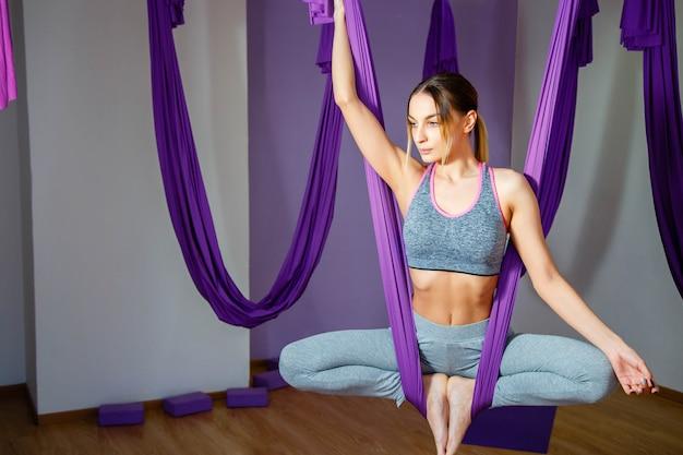 Die junge schöne jogifrau, die luftyoga tut, üben in der purpurroten hängematte im fitness-club. Premium Fotos