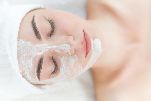 Die junge schöne mädchengesichtsmaskierung, die in den badekurortsalonaugen sich entspannt, schloss Premium Fotos