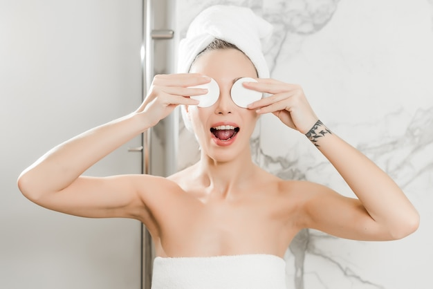 Die junge schönheit, die in die tücher im badezimmer eingewickelt wird, wendet baumwollauflagen auf augen an Premium Fotos