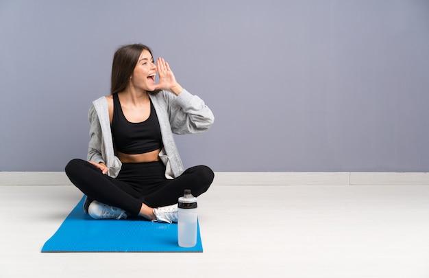 Die junge sportfrau, die auf dem boden mit der matte schreit mit dem breiten mund sitzt, öffnen sich Premium Fotos