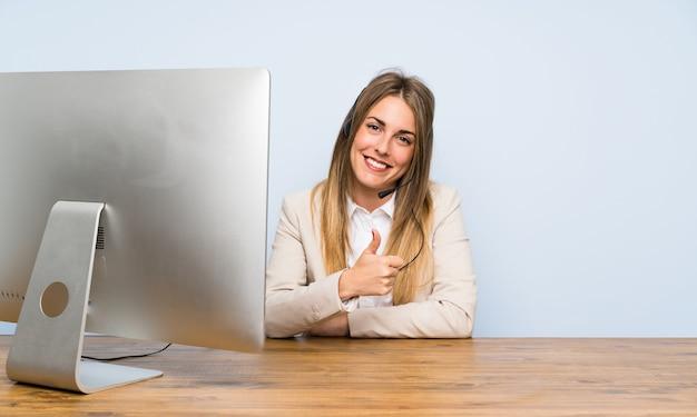 Die junge telemarketerfrau, die daumen gibt, up geste Premium Fotos
