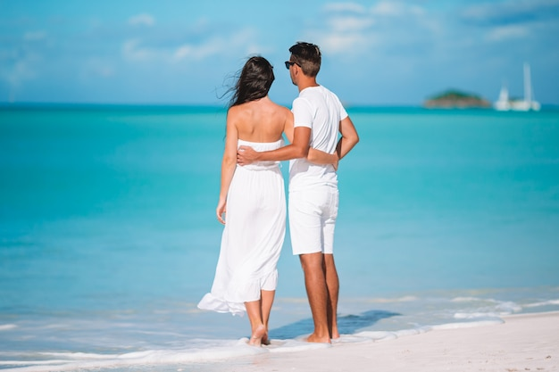 Die jungen paare, die auf tropischen strand mit weißem sand- und türkisozean gehen, wässern in antigua-insel in karibischen meeren Premium Fotos