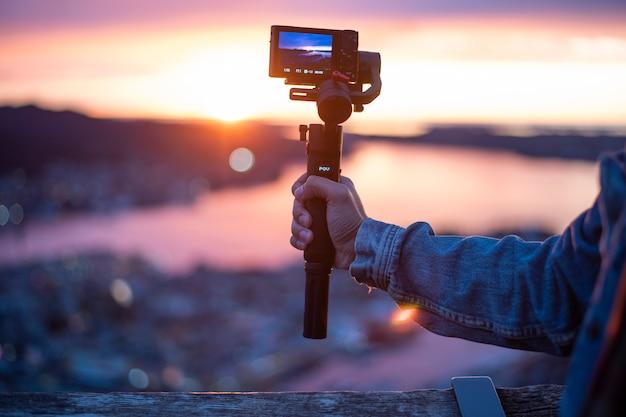 Die kamera am stabilisator zeichnet in der dämmerung eine wunderschöne aussicht auf Premium Fotos