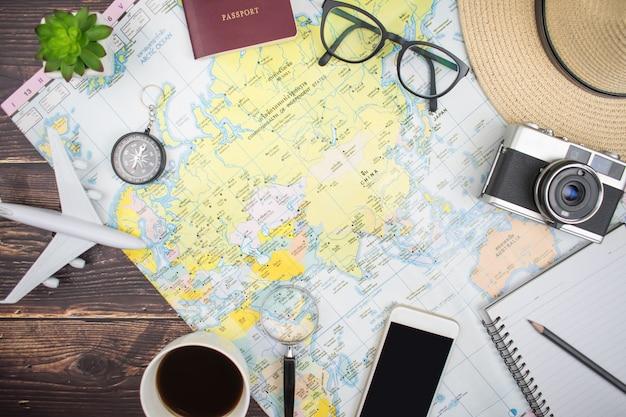 Die karte auf dem alten holztisch mit touristischem zubehör in der draufsicht, ebenenlage Premium Fotos