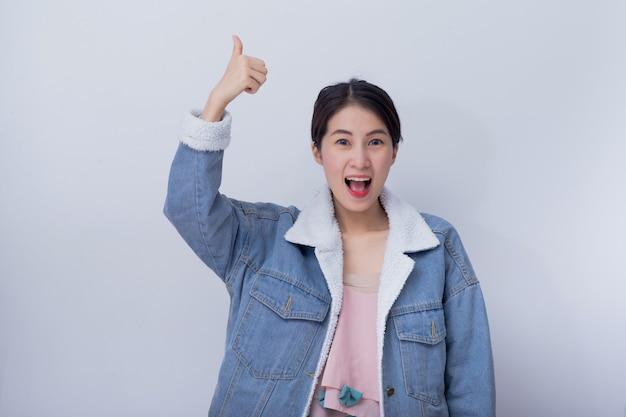 Die kaukasische lächelnde frau, die ihre hand zeigt, greift oben im guten job des konzeptes, das positive asiatische mädchen ab, das blaue zufällige kleidung trägt Premium Fotos