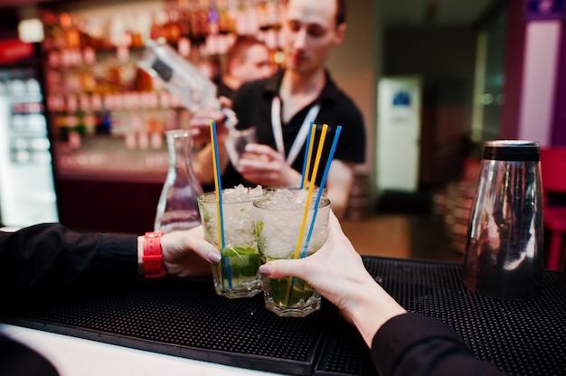 Die kellnerhände, die mojito coctails halten, trinken hintergrundbarmann bei der arbeit Premium Fotos
