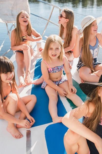 Die kinder an bord der seelyacht. die teenager- oder kindermädchen im freien. farbenfrohe kleider. kindermode, sonnige sommer-, fluss- und ferienkonzepte. Kostenlose Fotos