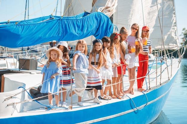 Die kinder an bord der seelyacht trinken orangensaft. die teenager- oder kindermädchen gegen blauen himmel im freien. farbenfrohe kleider. kindermode, sonnige sommer-, fluss- und ferienkonzepte. Kostenlose Fotos