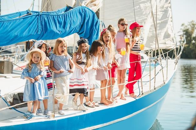 Die kinder an bord der seelyacht trinken orangensaft. die teenager- oder kindermädchen gegen blauen himmel im freien. Kostenlose Fotos
