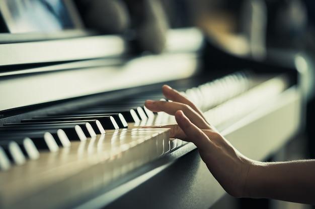 Die kinderhand, die musiktastatur spielt, schloss oben Premium Fotos