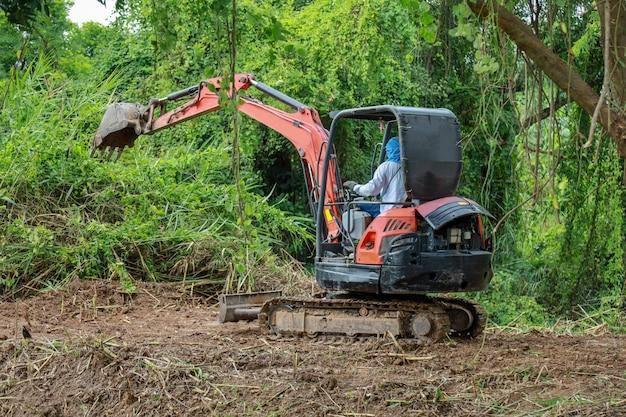 Die klare natur des mannantrieb löffelbaggers für machen die bodenstraße in thailand Premium Fotos