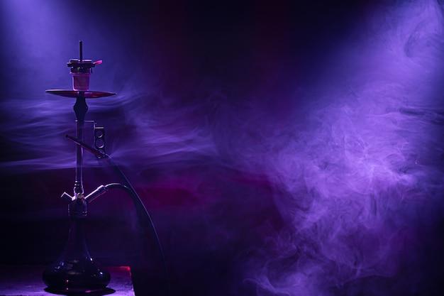 Die klassische wasserpfeife. schöne farbige licht- und rauchstrahlen. das konzept des shisha-rauchens. Kostenlose Fotos