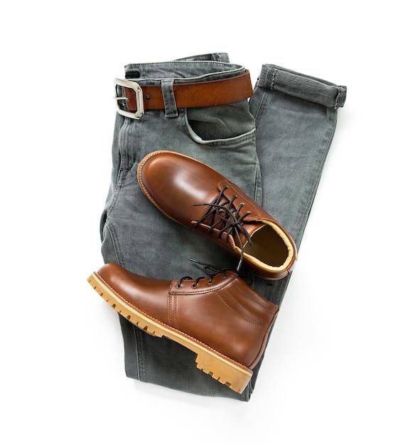 Die kleidung der männer stellte mit den braunen stiefeln, gurt und grauen jeans ein, die auf weißem hintergrund lokalisiert wurden. ansicht von oben Premium Fotos