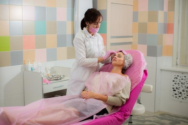 Die kosmetikerin behandelt vor dem eingriff die haut im gesicht ihres patienten. Premium Fotos