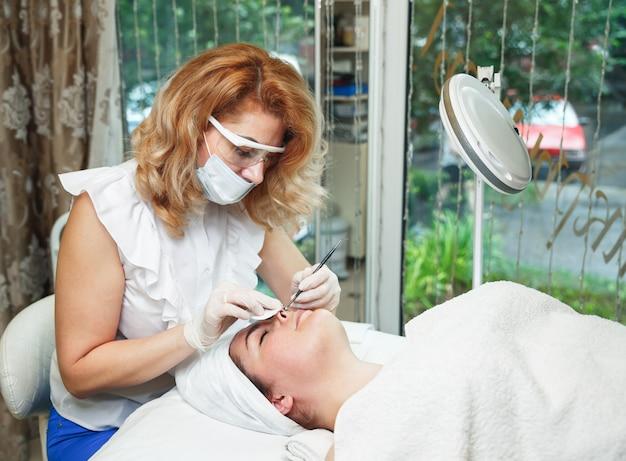 Die kosmetikerin drückt akne mit einer medizinischen nadel auf die stirn des patienten Premium Fotos