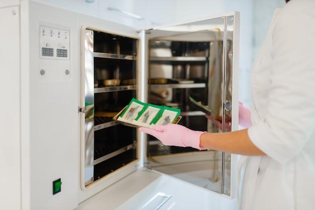 Die kosmetikerin in handschuhen legt maniküre- und pediküre-geräte in den antibakteriellen schrank Premium Fotos