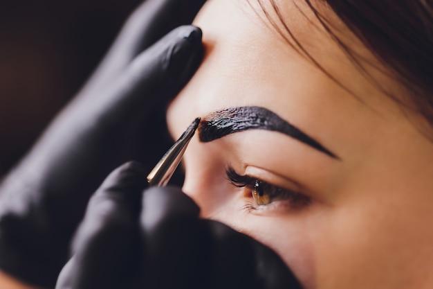 Die kosmetikerin und maskenbildnerin trägt in der sitzungskorrektur in einem schönheitssalon henna auf zuvor gezupfte, gestaltete, gestrichene augenbrauen auf. professionelle gesichtspflege. Premium Fotos