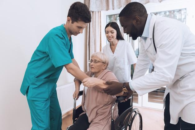 Die krankenschwester hilft einer älteren frau beim aufstehen Premium Fotos