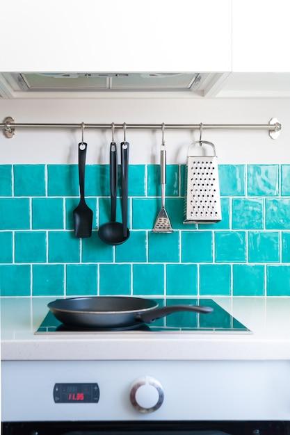 Die küche verfügt über dunkelgraue schränke mit flacher front, weiße quarzarbeitsplatten und eine glänzend blaue pflegekachel. Premium Fotos