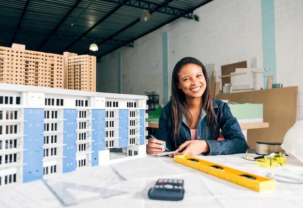 Die lächelnde african-americanfrau, die kenntnisse nimmt, nähern sich modell des gebäudes Kostenlose Fotos