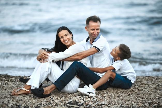 Die lächelnde familie sitzt am felsigen strand in der nähe des stürmischen meeres und umarmt eltern und kind Kostenlose Fotos