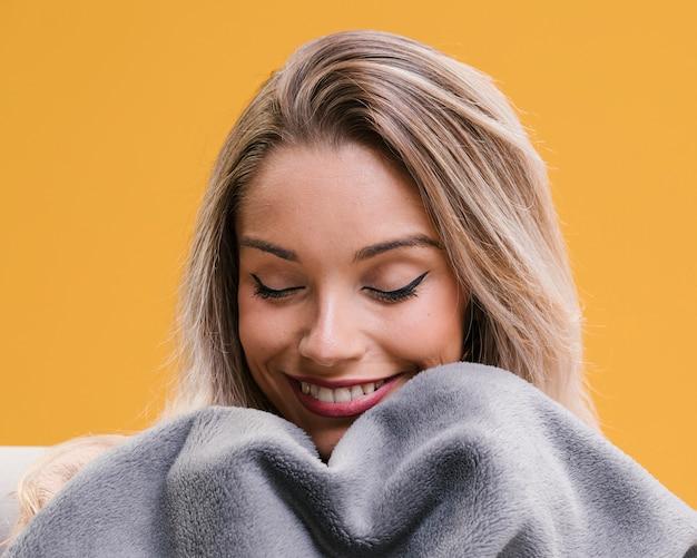 Die lächelnde frau, die decke mit augen hält, schloss zu hause Kostenlose Fotos