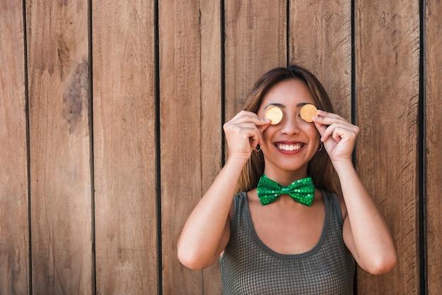 Die lächelnde frau, die goldene münzen hält, nähern sich augen Kostenlose Fotos