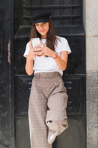 Die lächelnde junge frau, die vor schwarzem steht, malte simsende mitteilung der wand auf smartphone Kostenlose Fotos