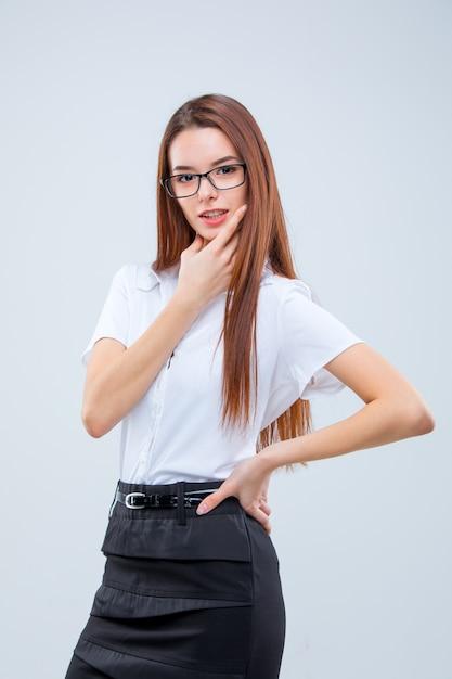 Die lächelnde junge geschäftsfrau auf grauer wand Kostenlose Fotos