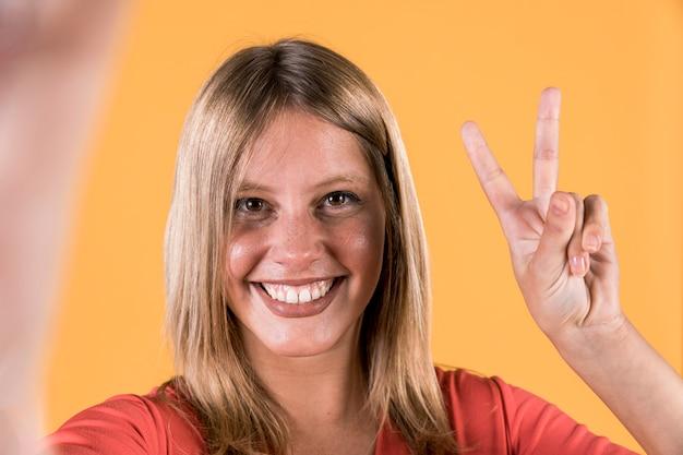 Die lächelnde taube frau, die sieg zeigt, kennzeichnen vorbei hellen gelben hintergrund Kostenlose Fotos