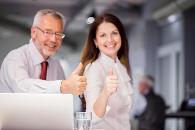 Die lächelnden erfolgreichen wirtschaftler, die daumen oben zeigen, unterzeichnen herein das büro Kostenlose Fotos
