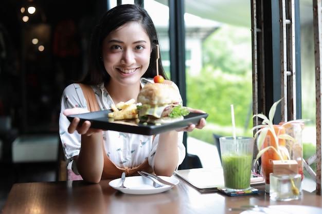 Die lächelnden und glücklichen asiatinnen und genossen, hamburger am kaffee und am restaurant zu essen, entspannen an sich zeit Premium Fotos