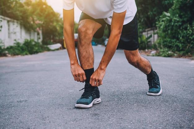 Die läufer, die in den schuhen gebunden werden, der mann, der auf der straße laufen, laufen für übung, laufsporthintergrund und nahaufnahme am laufschuh Premium Fotos