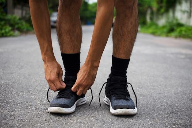 Die läufer, die in den schuhen gebunden werden, mann, der auf der straße laufen, laufen für übung Premium Fotos
